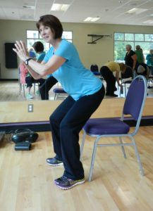 Female exercise instructor demonstrates proper squat form with chair.