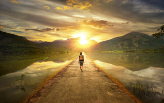 woman-walks-alone-down-a-road-toward-sun