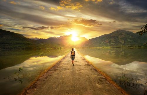 woman-walks-alone-down-a-road-toward-sun