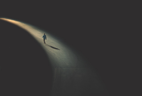 dark-scene-lone-man-in-beam-of-light