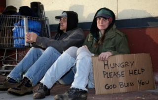 two-white-people-sit-with-sign-hungry-please-help-God-bless