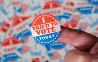 button says I tried to vote. Picture represents voter repression.